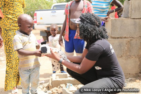 Nikki Laoye giving a toy to a displaced child