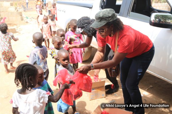 Nikki and Faith Yebo distributing food and toys to the children
